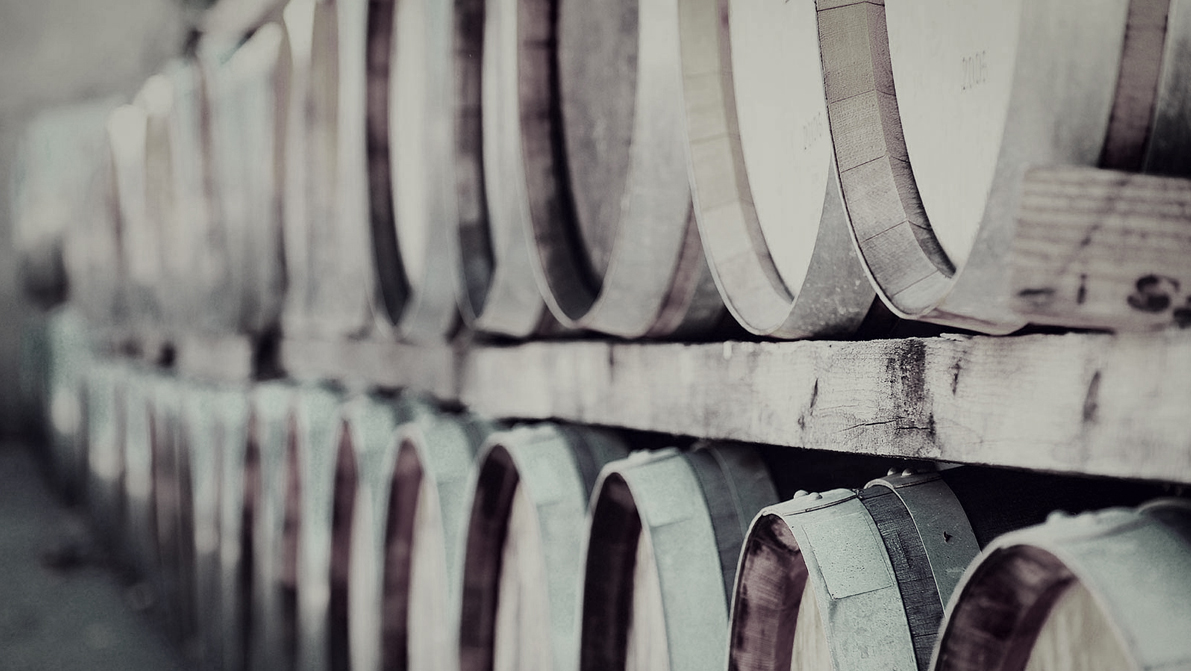 image of wine barrels stacked on wood